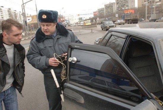 Инспектор ГИБДД проверяет коэффициент светопропускания
