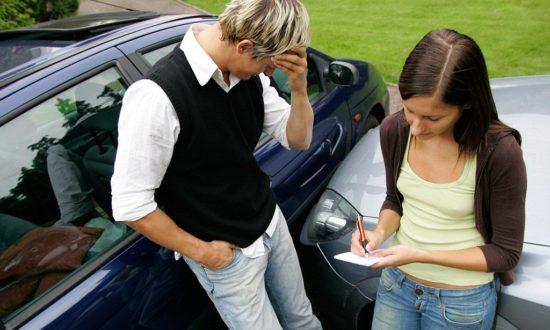 Два водителя стоят возле машин после аварии