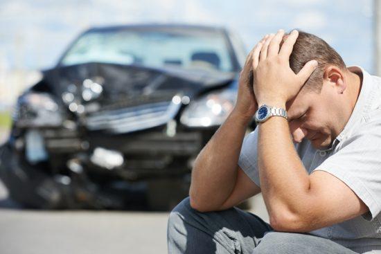 Мужчина, обнявший голову руками на фоне разбитого автомобиля