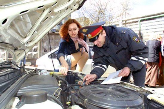 Эксперт осматривает автомобтль при перерегистрации