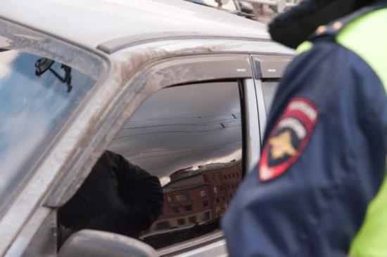 Сотрудник дорожной полиции возле автомобиля с тонированными стёклами