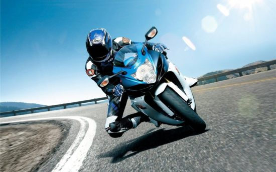 Мотоциклист на повороте в лучах солнца