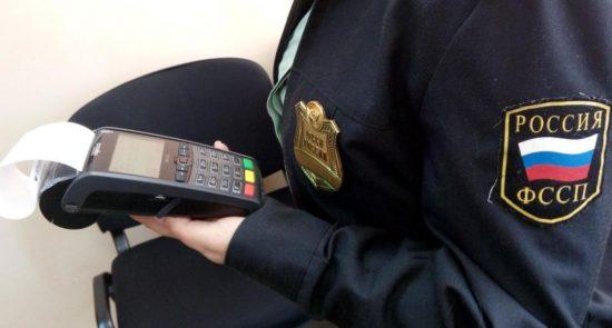 Инспектор ФССП держит в курах кассовый аппарат