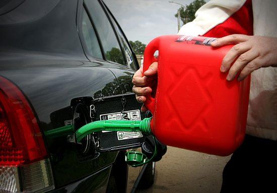 Машину заправляют бензином из канистры